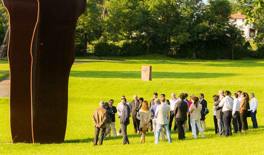 Grupo visitando Chillida Leku bajo la sombra de Buscando la luz I (acero corten, 1997). ©Zabalaga Leku. San Sebastián, VEGAP, 2019. Sucesión Chillida y Hauser & Wirth. Foto Mikel Chillida