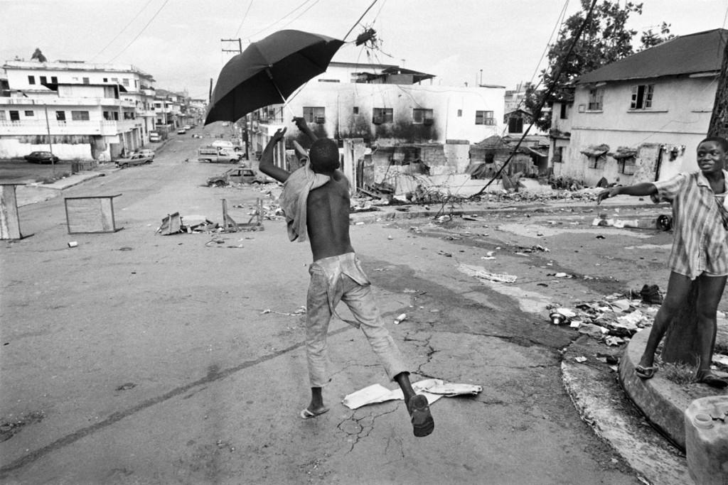 Gervasio Sánchez. Un niño juega con un paraguas en la avenida principal destruida por los combates Monrovia (Liberia), 1996