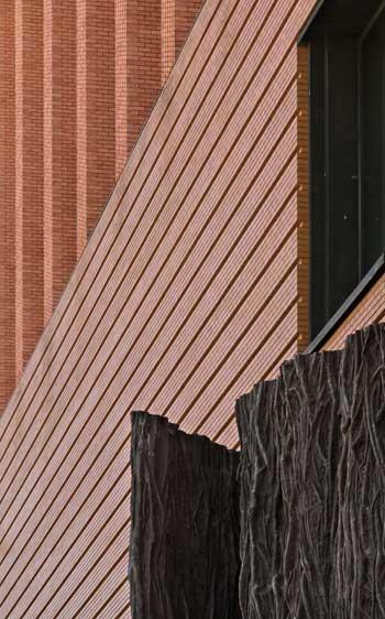 A vueltas con los orígenes de la arquitectura. Puerta leñosa en bronce de Cristina Iglesias, muro llagado de ladrillo aplantillado y logia de pilares áticos. © Joaquín Berchez. 2017