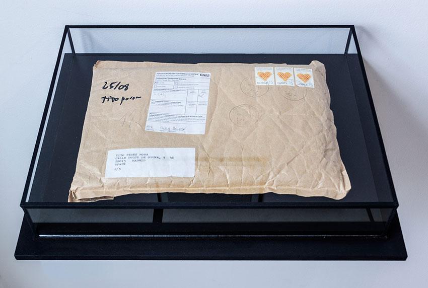 S/T, instalación: papel de aluminio mecanografiado, bandera, sobre de kraft, urna de vidrio 75x45x35 cm. Tito Pérez Mora, 2015. Foto: Daniel Vega Borrego